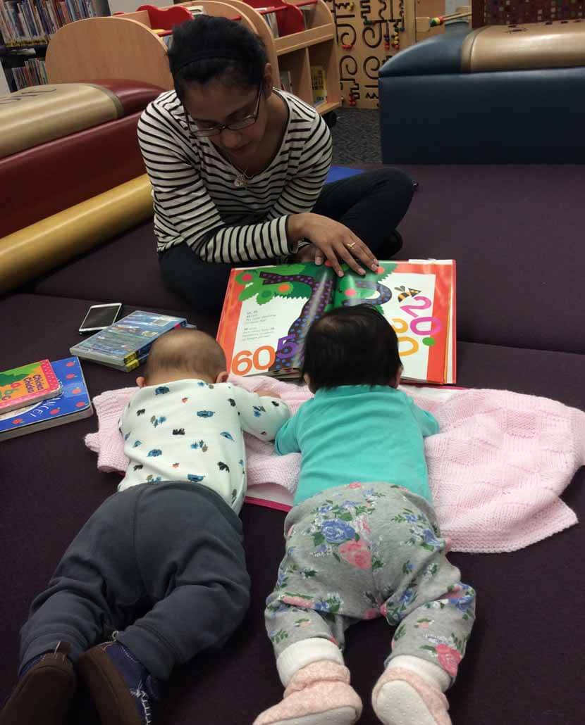 woman reading to two babies